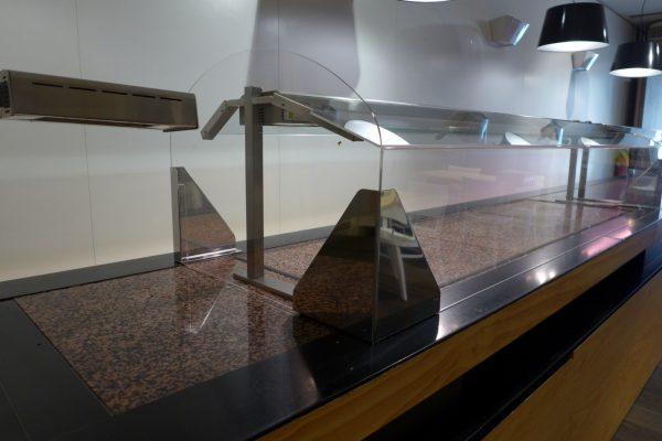 Detalle de las escuadras de acero inox como soportes de mampara de protección anticontagio para hostelería instalada en el mostrador de un emblematico bufette