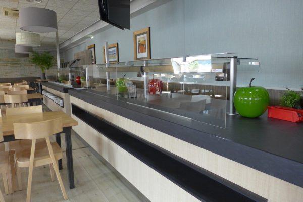 Vista detalle de mampara de protección en barra de restaurante autoservicio