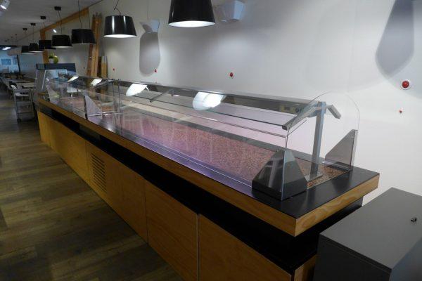 Mampara de protección anticontagio para hostelería instalada en la barra de un bufette.