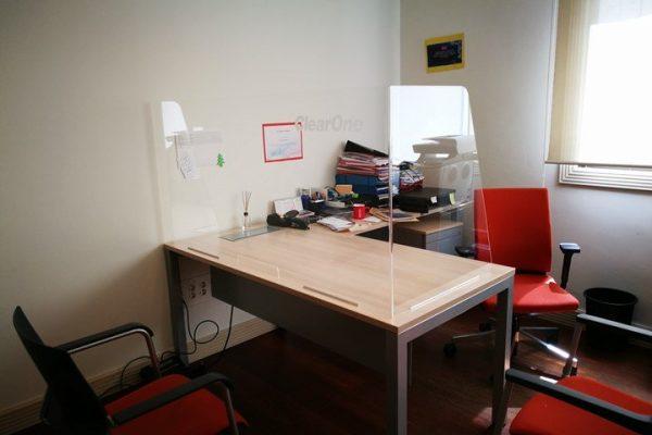 Mampara de protección anticotagio con pliegues laterales sobre mesa de despacho